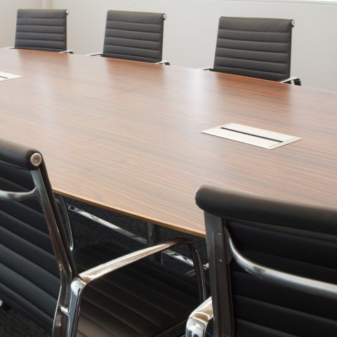 Woodgrain laminate boardroom with solid stained to match sharknose & cable box intergration